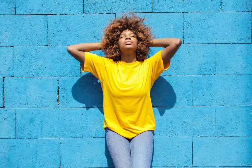 woman standing beside blue concrete wall