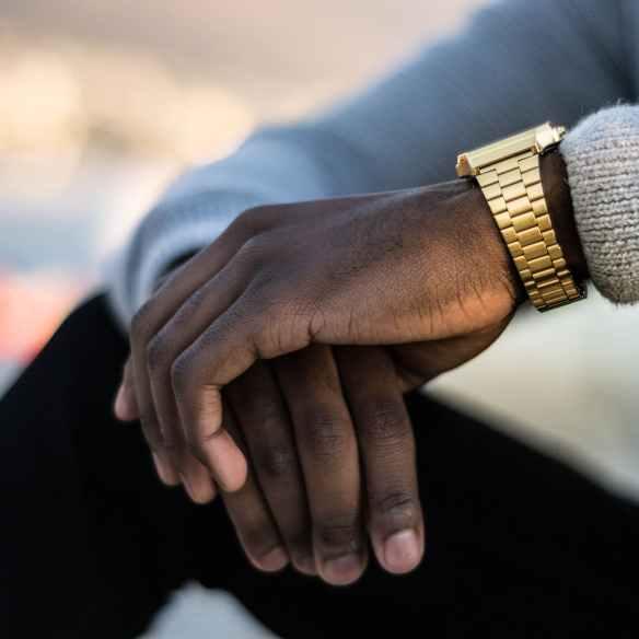 man wearing gold colored wristwatch